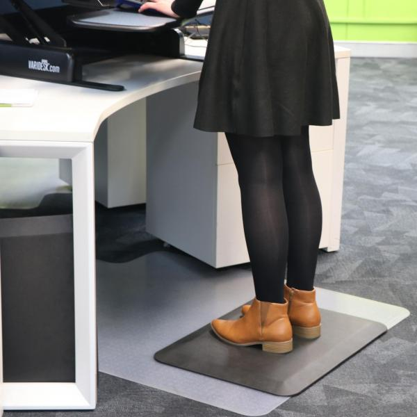 a woman in a black skirt, black tights and brown boots stands on an anti fatigue mat (the comfort stand plus) while working at a stand up desk.
