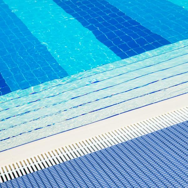 The edge of a swimming pool with steps leading down to the bottom. The Sure Grippa is laid along the edge to prevent slips and a drain runs inside that to remove water overflow.