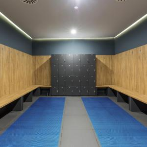 A locker room with wooden benches around the outside and a block of lockers at the end. The floor is tiled with Sure Grippa non slip matting laid in two strips covering most of the floor except the centre.