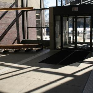 The entrance to a public library with shadows cast by a bright sunny day.
