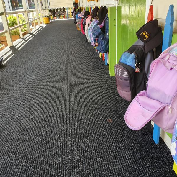 Children's bags are hung on pegs along an empty corridor. On the floor is the Dura Rub heavy duty entrance mat.