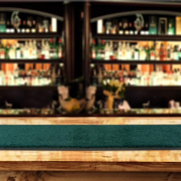 A green bar runner is laid on a bar top with an out of focus bar area behind.