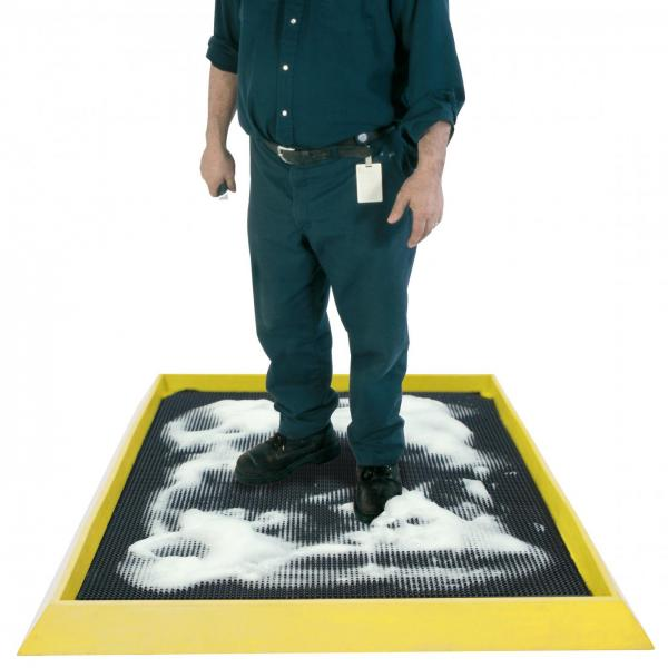 a man stands on the boot dip surrounded by soap suds for an intense clean. The boot dip mat has a black surface and a raised edge to keep the soap and water in the mat.