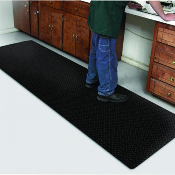 the diamond foot anti fatigue mat is laid under a mans feet as he works at a bench with draws either side