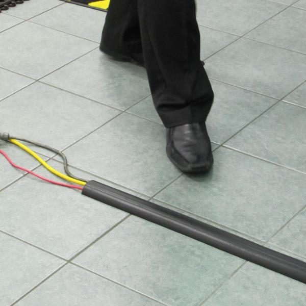 A cable protector is laid on a pavement over 3 wires. A person is bout to step over the wires safely thanks to the cable protector.