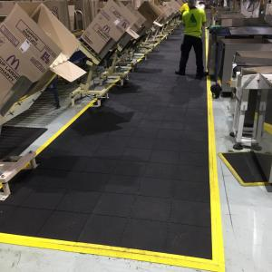 The comfort link is laid down a warehouse aisle where cardboard boxes are being loaded from conveyer belts. A man is working on the black anti fatigue mat.