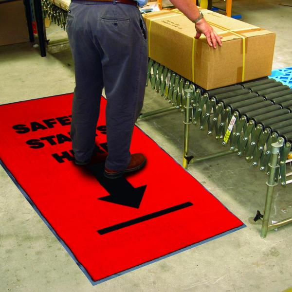 a man stands on a safety mat while seeing to a package on a conveyer belt.