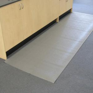 a grey anti static mat is laid on the carpeted floor in front of a wooden cupboard.