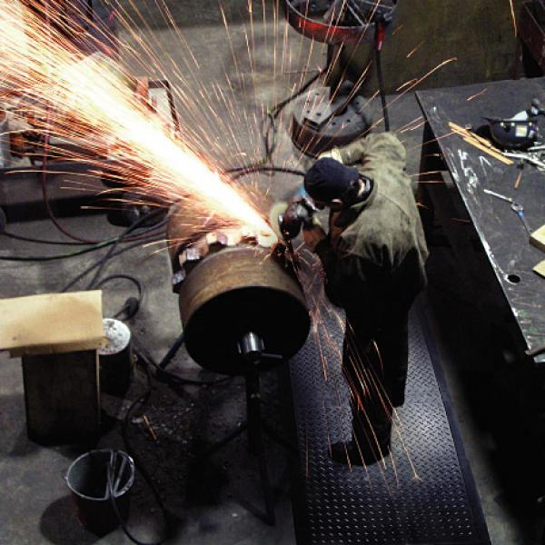 a welder creates sparks while wearing safety gear and standing on a welding safety mat