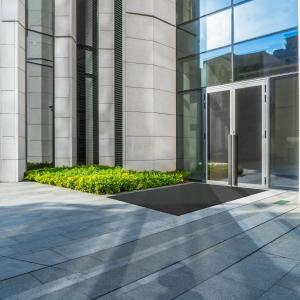 The opti-scrape is laid outside a glass door to a fancy office building. The floor is stone slabs and the walls are smooth white brick.