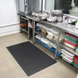the cushion ease anti fatigue non slip mat is laid in a busy commercial kitchen. The mat is black with holes for drainage.