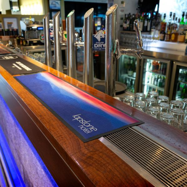 Printed Bar runners are placed along the front of a bar top. One is printed with the logo of a hotel and the other is printed with a coffee roaster logo.