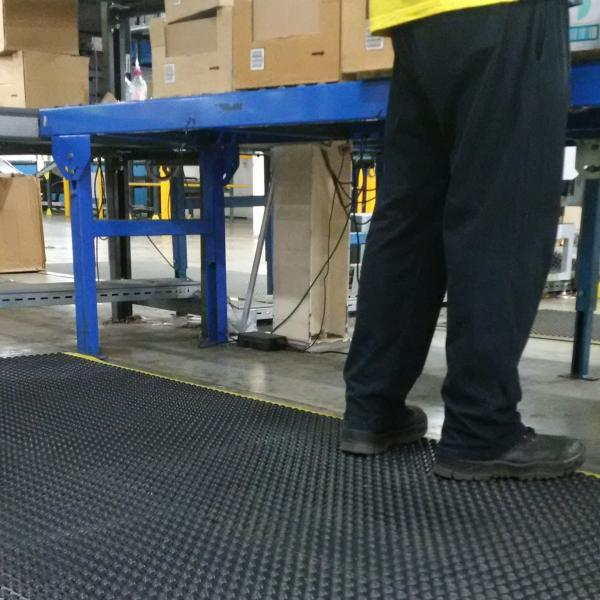 a pair of legs in black trousers, black workbooks and a yellow high visibility jacket is standing on a heavy duty anti fatigue comfort mat. There is a table stacked with boxes in front of them and a conveyer belt to their right.