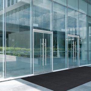 Outside a smart glass entranceway is a tiled floor topped with a modular entrance mat. The tiles interlock to form one large entrance mat.