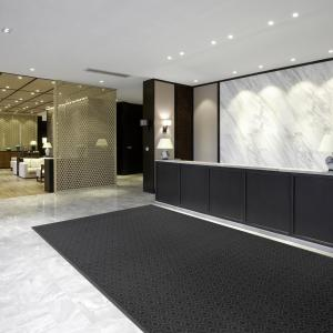 The Glamour Step entrance mat is laid in the reception area of a hotel. The reception has marbled white walls and floors with a black counter, and a lobby with sofas can be seen in the background.