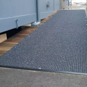 Non Slip Matting - the Ultra Grip - is fitted onto a ramp outside a temporary classroom.