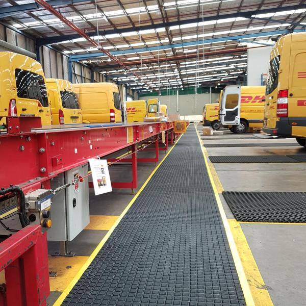 The Air Grid anti fatigue and non slip mat runs between two rows of yellow DHL vans that back onto a walkway