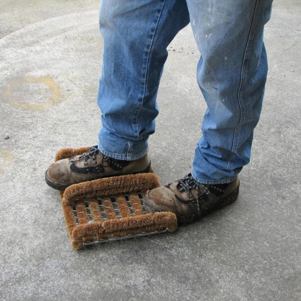 A man scrapes his workbook on the Boot Scraper. He is wearing blue jeans and is standing on a concrete floor.