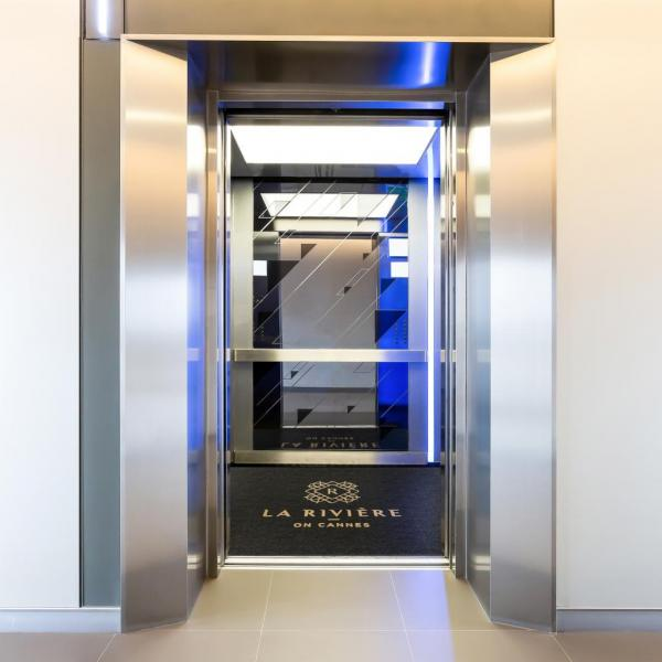 A lift mat is printed with the branding of La Riviere apartment block in the Gold Coast. The name and logo is printed in gold, the mat itself is charcoal and fitted into a lift floor.